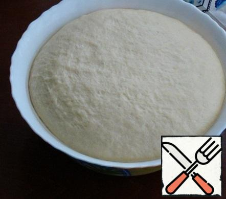 After about an hour, the dough came up perfectly. It must be kneaded and divided into equal pieces. They also need to be rounded and covered with a napkin, leave on the table.