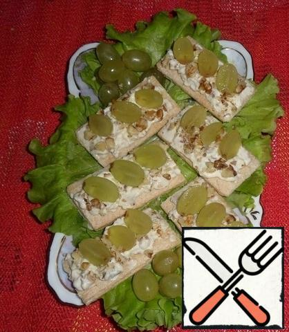 Grapes are washed, dried, cut lengthwise into 2 parts. Halves of grapes decorate bread with cheese appetizer.