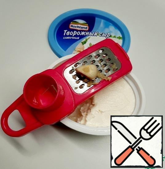 Garlic grate on a fine grater and mix with cottage cheese.