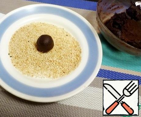 Lightly fry the sesame seeds of  in a frying pan. From the chocolate mass, roll the balls and roll in sesame seeds. To make sure that the candies are the same, I advise you to weigh them. I got 14 candies of 12-13 grams each.