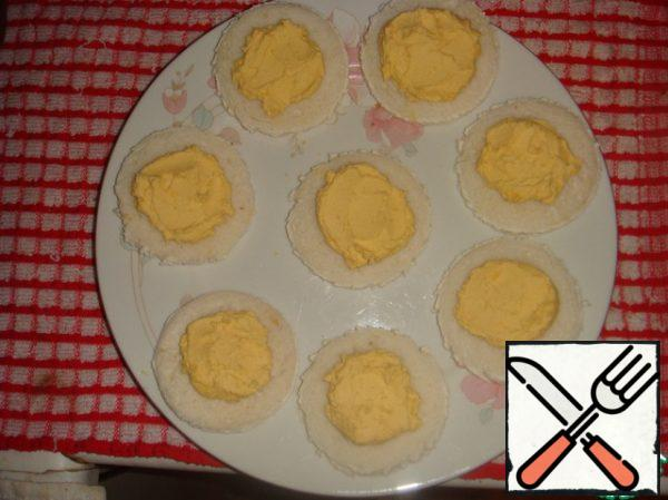On each bread circle, place a low mound of cream-yolk mixture in the middle.