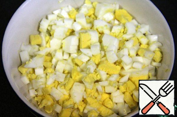 Boil the eggs and cut them into small cubes.