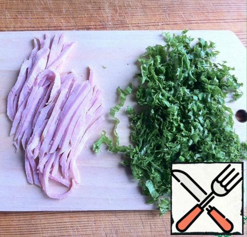 Ham and lettuce leaves are cut into strips.