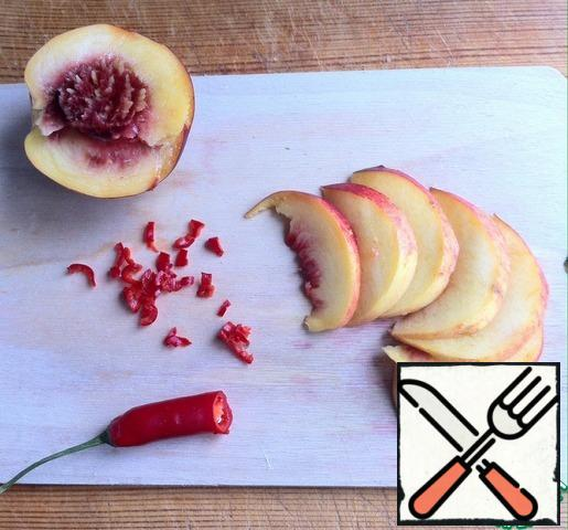 Nectarine cut into slices. Remove the seeds from the chili pepper and finely chop it.