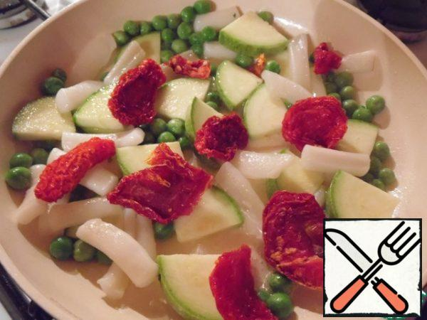 To the squid, add the zucchini, peas and dried tomatoes, cut into quarters, and fry for 3-4 minutes.