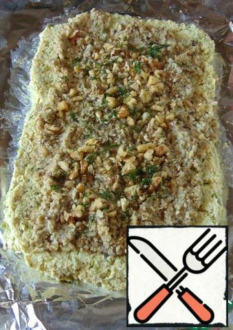On a sheet of foil or food film, we put minced meat with peas. Stepping back from the edges, we put the mushroom filling with rice. Sprinkle the filling with chopped nuts and finely chopped dill. Roll it up. We put the roll in the cold for an hour.