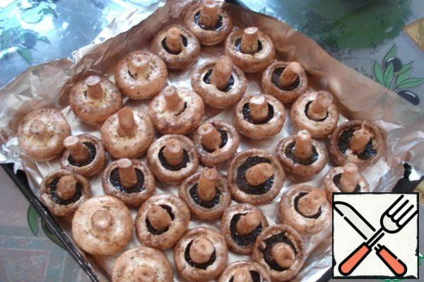 Wash the mushrooms, dry them on a towel, put them in a bowl, pour oil, lemon juice, salt and sprinkle with spices. Let stand for an hour. If the mushrooms are large - two hours. And if they are small, then half an hour will be enough. Place on a baking sheet. I lubricate the foil with oil.
