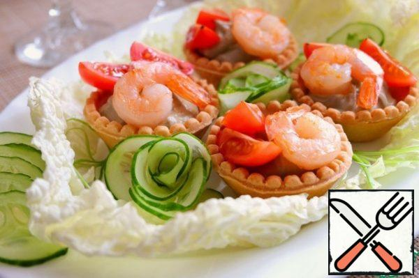In tartlets, put the cream of avocado and garlic, add shrimp, cherry tomatoes slices. Place fresh lettuce leaves on a platter. Add to the snack decorations in the form of roses from fresh cucumber.