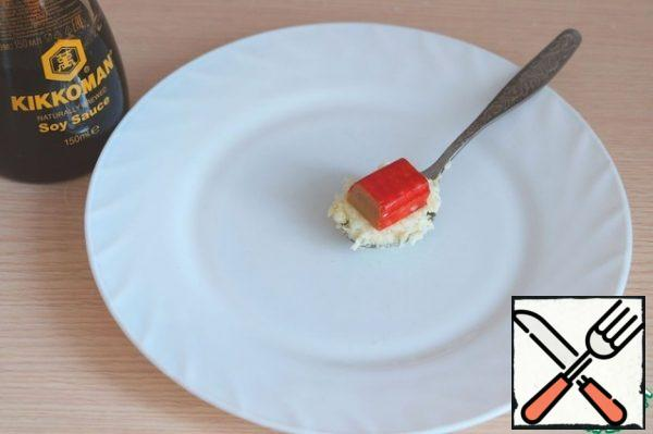 Take a teaspoon of the required amount of cheese-egg mixture, add a cube of crab stick.