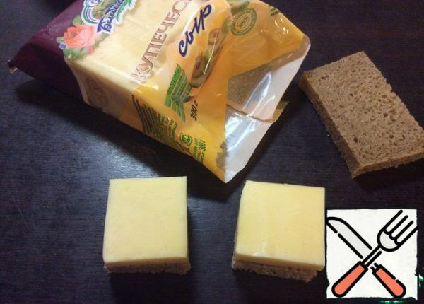 Cut the crust off a slice of bread. Put a piece of cheese on a piece of bread, adjust the size of the slice and cut each slice of bread into 4 parts.