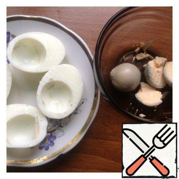 Peel the eggs and cut them lengthwise. Carefully remove the yolk and transfer it to a bowl.