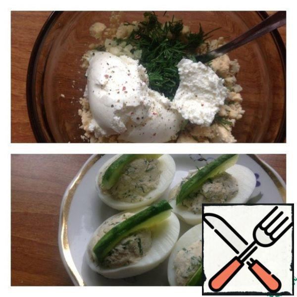 Chop the yolk with a fork. Add to it cottage cheese, garlic passed through a press, salt, pepper and dill finely chopped. Mix everything thoroughly. If desired, you can add a spoonful of mayonnaise. Stuff the eggs with the filling. Cut the cucumber into slices and stick it in the center of each half of the egg. Garnish with a sprig of dill.