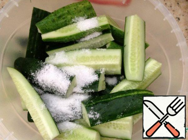 In cucumbers, cut off the buttocks and cut the cucumbers themselves into cubes. Put it in our bowl. Pour salt and sugar on top of the cucumbers. Close the lid tightly.