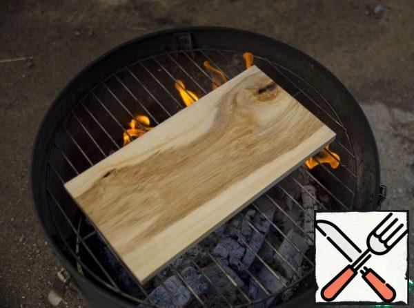 After the coals have reached the optimum temperature, place the grill board on the grill grate, over the coals, face down. In this position, hold the board for 1-2 minutes, until the smoke goes out (the dried front side will not allow the grill board to bend excessively during baking).