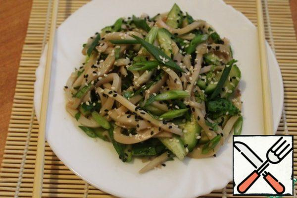 In a bowl, mix the herbs, squid and cucumbers, pour soy sauce and sesame oil. Sprinkle with a mixture of black and white sesame seeds. Asian-style squid salad is ready!