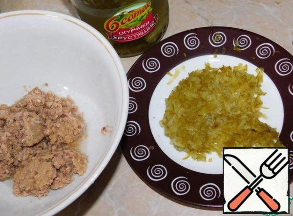 Mash the tuna with a fork and add the grated pickled cucumbers to it.