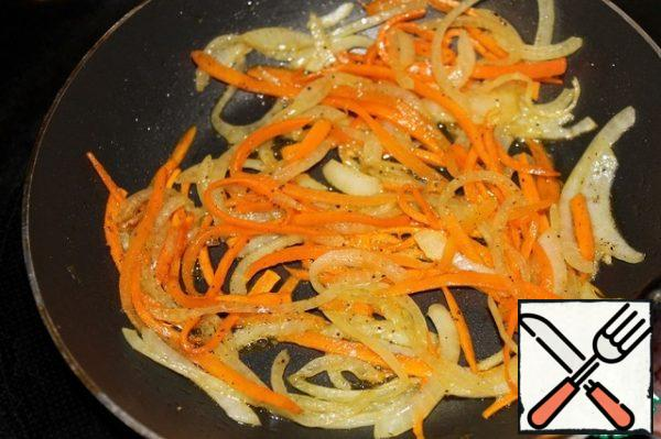Cut the onion into half rings, cut the carrots into thin strips, and fry until slightly golden brown. Cool down.