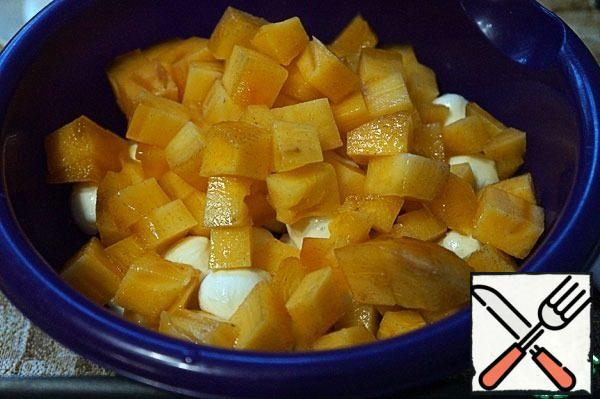 Cut the persimmon in half, release the pulp, cut into cubes, add to the tangerines and cheese.