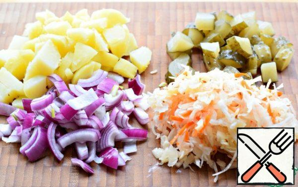 Cut the potatoes into arbitrarily large pieces. Cucumber is also cut into large pieces. Onion-quarter-rings. Lightly squeeze the cabbage from the brine. (I recommend large cuts of vegetables for this salad).