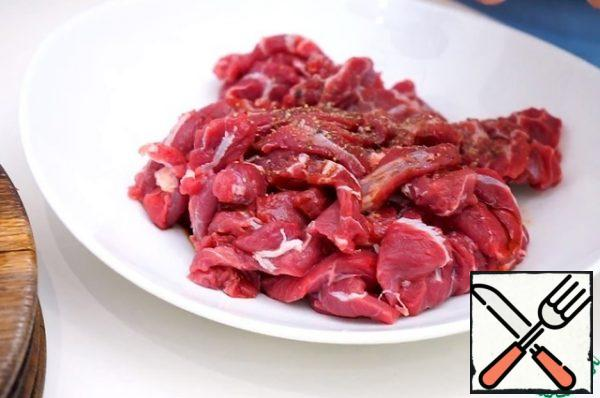 Cut the beef into thin slices 0.5 cm thick, pepper and marinate the meat in a spoonful of soy sauce.