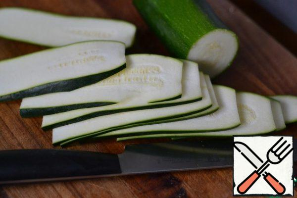 Cut the zucchini into thin strips. Lightly season with salt and pepper.