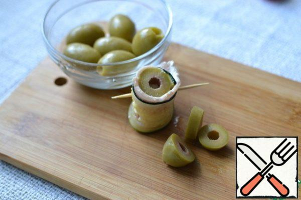 Cut the olives. Insert one piece into the roll.