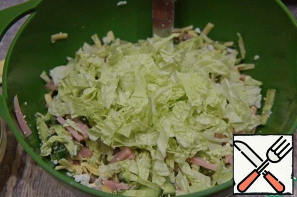 Peking cabbage leaves cut into wide strips and pour into a bowl with the salad.