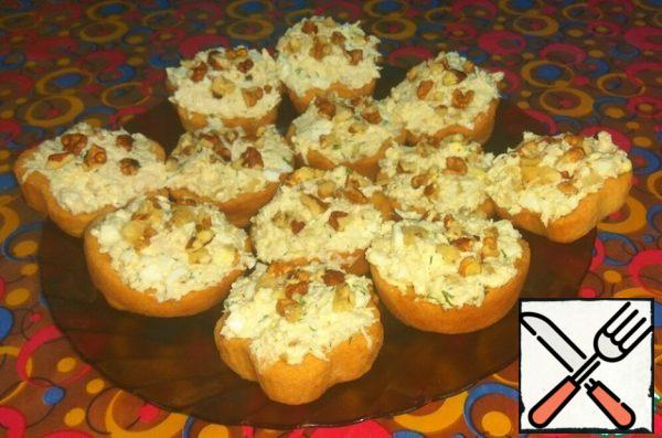 In the cooled tartlets, spread out the finished salad, sprinkle with finely chopped nuts. From the specified number of ingredients, I got 15 tartlets.