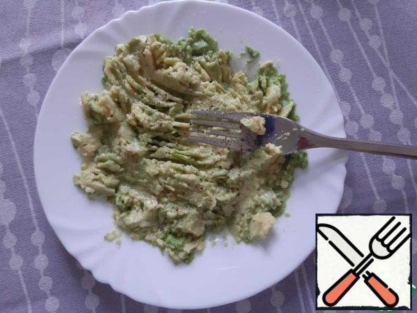 Cut the avocado in half. Use a spoon to get the avocado pulp. Mash with a fork. Pour over the lemon juice.
