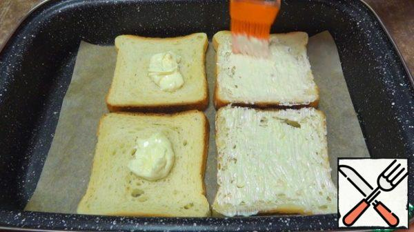 Mayonnaise-garlic mixture spread on slices of dried bread and spread over the entire surface.