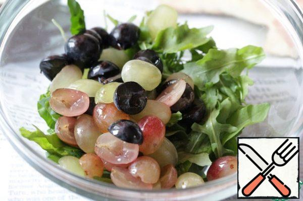 Wash the grapes and dry them. If it is large and with bones, then cut it into halves and remove the bones, small boneless grapes can be added to the salad as a whole.