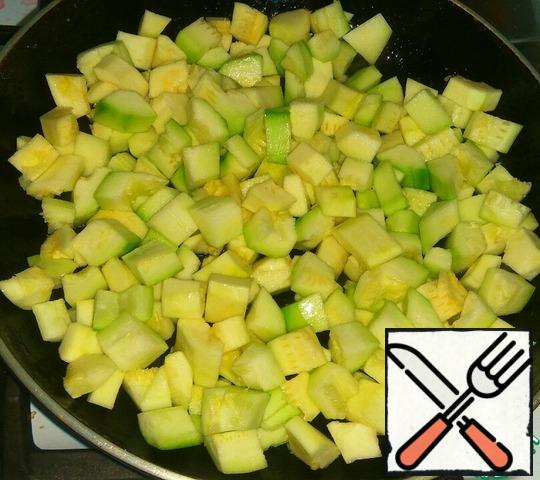 Peel the zucchini and remove the seeds. Cut into small pieces. Fry in vegetable oil for 5 minutes.