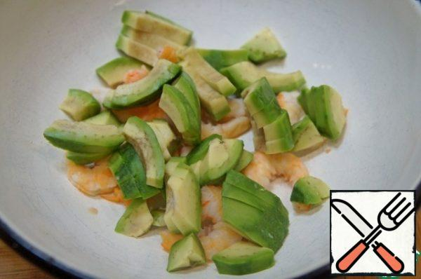 Cut the avocado lengthwise into 4 pieces, remove the stone, peel and cut crosswise into slices. Add to the shrimp.