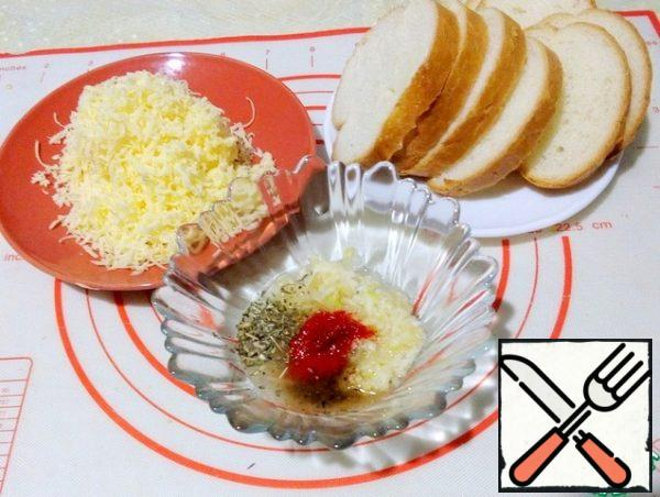 Cut the baguette into slices 1 cm thick, grate the cheese. Prepare garlic sauce: in a bowl, combine and mix - crushed garlic, paprika, Italian herbs, a mixture of peppers and dilute with broth.