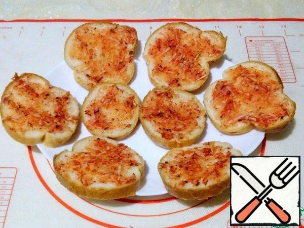 Spread the garlic sauce over the baguette slices.