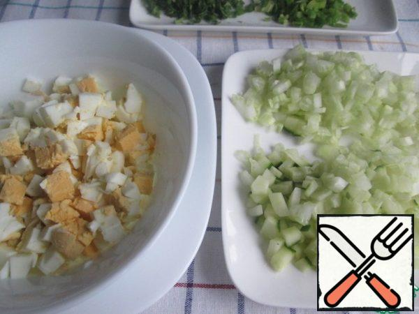 Finely chop the eggs. Cut the cucumber and celery into small cubes. Cucumber, if desired, can be cleaned. Finely chop the dill and green onions.