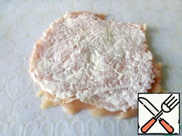 Cut the chicken breast not completely along the entire length and unfold it like a book. Lightly beat off the flat side of the hammer, season with salt and mayonnaise. You can replace it with yogurt or sour cream.