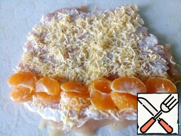 Grate the cheese and sprinkle on top. Disassemble the tangerines into slices and spread out on the edge.