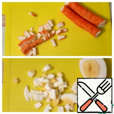 Chop the crab sticks and boiled eggs finely.