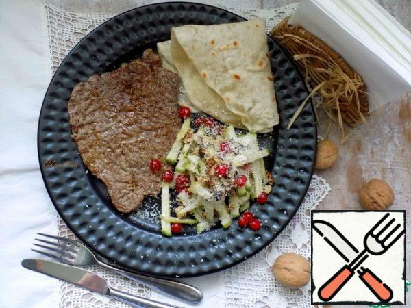Put the salad in a plate, sprinkle generously with coconut shavings. I'll serve it with marbled beef fried in a grill pan. I will complement the dish with homemade pita bread.