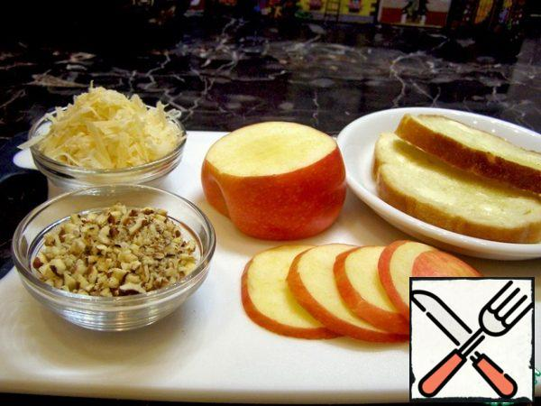 Cut the apple into thin slices, grate the cheese on a coarse grater, chop the nuts, lightly brush the pieces of bread with butter.