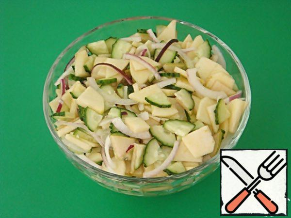 In a bowl, mix the slices of cucumbers, pears, apples and onions.