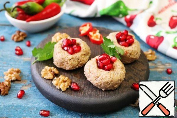 Place in the refrigerator to cool. To serve, roll the balls, the size of a large walnut, and flatten them. Make a small dent on top and put the pomegranate seeds in it. You can decorate with herbs or halves of walnuts.