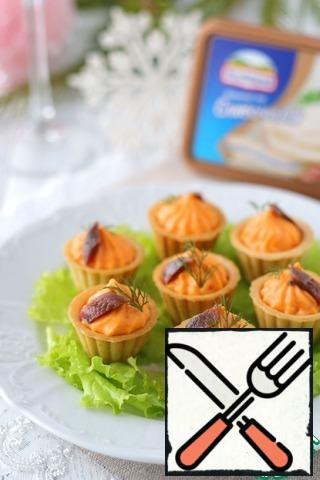 Add the prepared cream using a pastry bag to the tartlets. Put the anchovies preserved in oil on a paper towel to remove excess oil, then cut into pieces. Add the anchovy slices to the cream. Decorate tartlets with cheese cream with fresh dill greens.