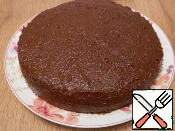 With a smaller part of the cream, we will smear and level the surface of the cake, slightly lubricate the sides to hide the seams.