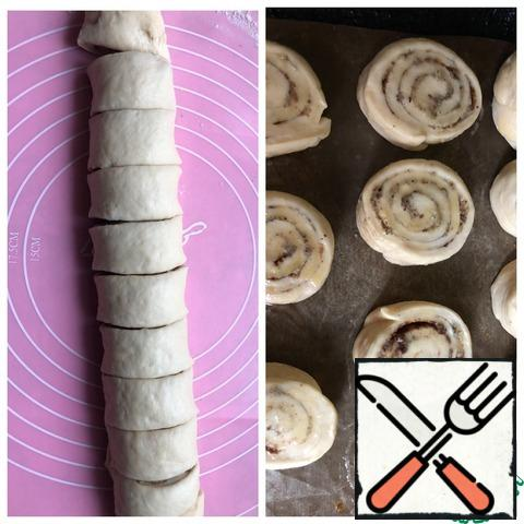 Cut the roll into portions and place on a baking sheet covered with a baking mat. Cover the buns with a towel and let them rest for 20 minutes.