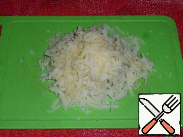 Grate the potatoes on a coarse grater. Finely chop the greens.