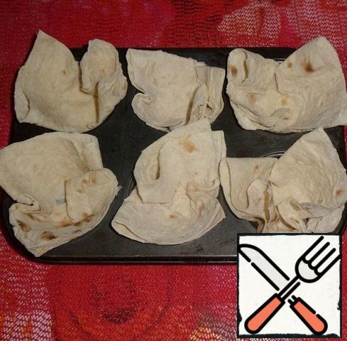 Pita bread sheets are placed in a baking dish for portion cupcakes. These are the baskets you get.