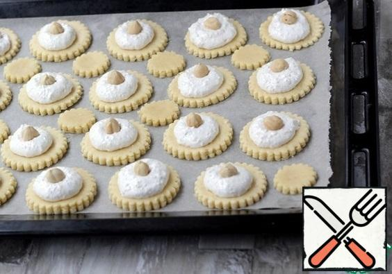 Put the protein mass in a pastry bag and put it on the cookies. Put a nut in the middle.