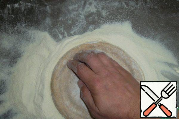 """Pour the mixture on the table. The workpiece is slightly flattened with the palm of your hand, maintaining a round shape. We plan the sides. Just squeeze out the """"circle"""" with your fingers at a distance of 1 cm from the edge of the workpiece. This is not necessary at all. After a few hundred rolls, the cooks stop doing such nonsense, but it's easier for beginners..."""